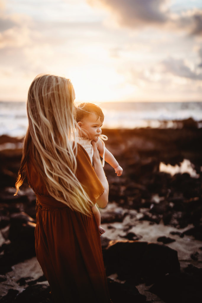 Family Photography, woman holds her young sun at sunset at the ocean