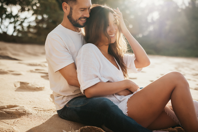 Elopement Photography, woman leans back in man's arms as they sit on a tropical beach in the sand
