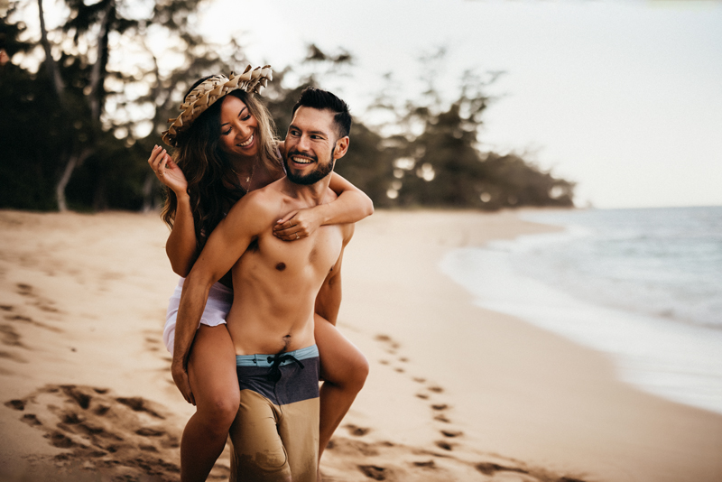 Elopement & Family Photography, man carries woman on back on the tropical beach near shore