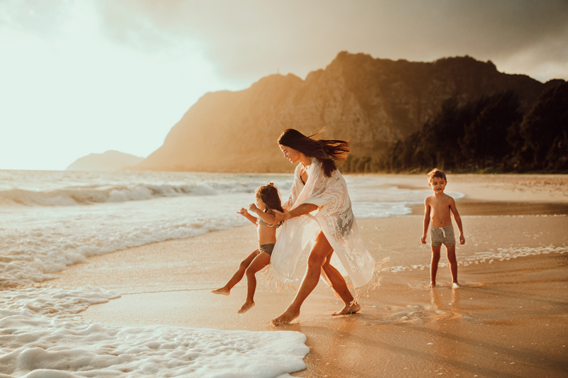 Family Photography, smiling woman lifts young daughter near beach waves, her son walks behind her