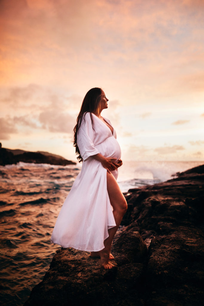 Family Photography, pregnant woman in white dress holds belly, she stands in the ocean