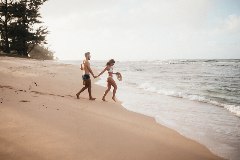 Elopement Photography, woman leads man across Hawaii beach to the calm waves of the ocean